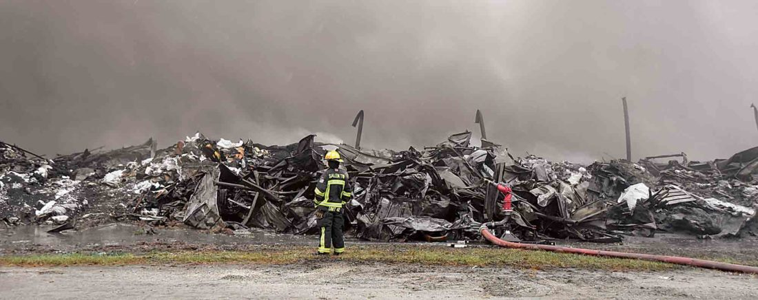 A Salem Township firefighter waits on water to arrive via tanker at the smoldering remains of the former Ames Plant on Old Camden Avenue Monday. (Photo by Jeff Baughan)