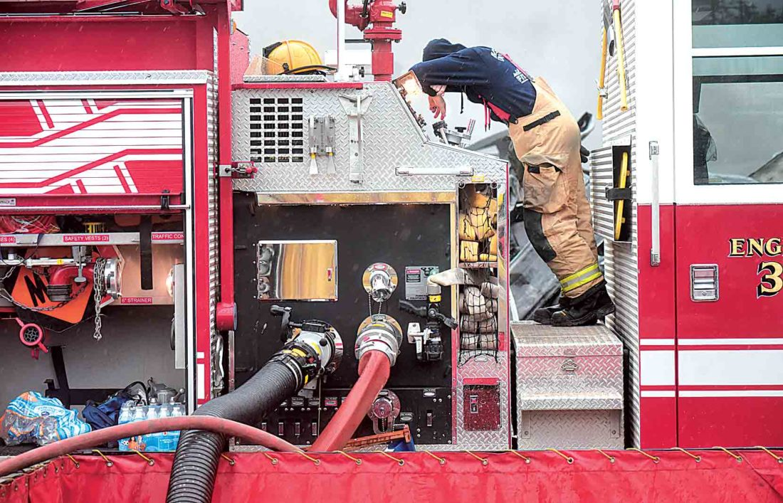 A Lubeck Volunteer Fire Department firefighter rests as he awaits more tankers to arrive with water Monday. (Photo by Jeff Baughan)