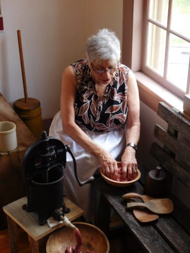 Kathleen Backer makes sausage the old-fashion way at the Kiesling House. The old hand crank machine requires a good deal of upper arm strength. This is the second time the Kiesling house has held this program. Backer said it was easier to work the equipment the second time around.  Staff photos by Clay Schuldt
