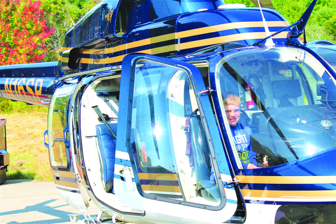 Photo by Jordan Patterson: Avery Emmick testing out the New York State  Troopers Helicopter at the 100th Anniversary Open House.