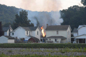 A fire burns at the site of a freight train derailment, Wednesday, Aug. 2, 2017, in Hyndman, Pa. A freight train carrying hazardous materials partly derailed early Wednesday, setting train cars and a garage on fire and prompting emergency officials to evacuate nearby residents. (Steve Bittner/The Cumberland Times-News via AP)
