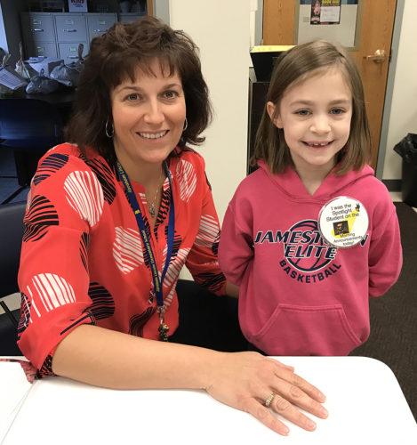 "Lincoln Elementary School Principal Katie Russo congratulates ""Spotlight Student"" Annika Ricker."