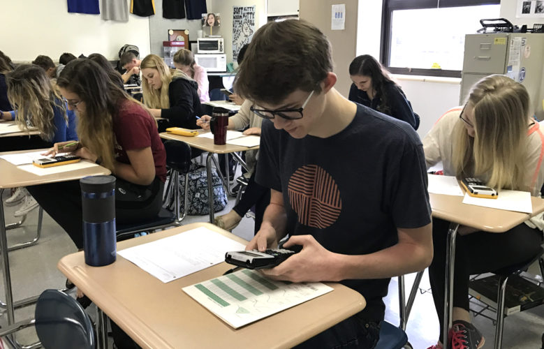 Jamestown High School senior, Spencer Higbee, works on a problem during Chris Maggio's Elementary Statistics class. Elementary Statistics is one of the many JCC College Connections courses offered to JHS students to help them receive college credit while still attending high school.