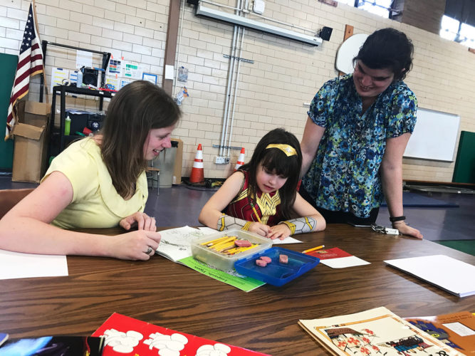 """Bush Elementary School music teacher Kathy Brunco works on """"how-to draw a superhero"""" with Bush student Alexandria Braymiller and her mom, Michelle, during the school's recent Family Literacy Night."""