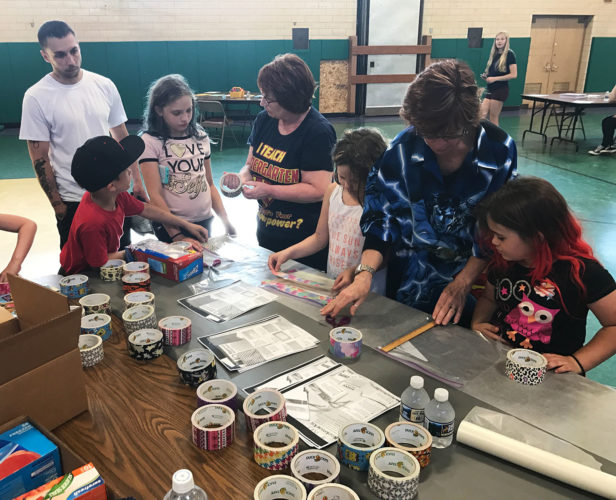 Bush Elementary School dad Wayne Snyder watches as Bush students Corry Seeking, Bionca Clifton, Clair DeVilieger and Myamee Seekings work with Bush Elementary School teachers Eileen Healy and Carrie Blitz to create duct tape pencil pouches during the school's recent Family Literacy Night.