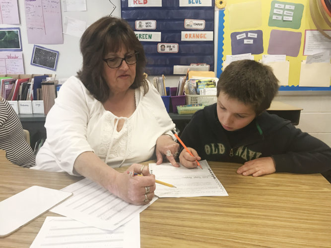 Bush Elementary School paraprofessional Lorri Papaserge works with third-grader Josiah Senear on two-step math word problems that involved two different operations during a small group session.