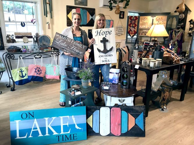 Re-Imagine, an eclectic store in Bemus Point, offers a variety of items including custom signs, vinyl decals and consigned art pieces from local artists. Pictured from left are Angie Lipari and Brenda Gernatt, store co-owners, with a few of their custom signs.  P-J photo by Katrina Fuller