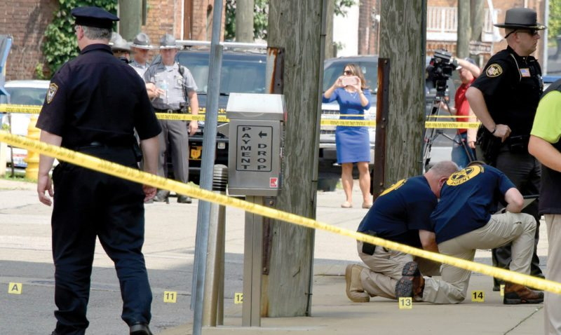Evidence markers are placed on North Court Street and the sidewalk next to the Jefferson County Courthouse in Steubenville, Ohio, after Jefferson County Judge Joseph Bruzzese Jr. was ambushed and shot early Monday morning. (Darrell Sapp/Pittsburgh Post-Gazette via AP)