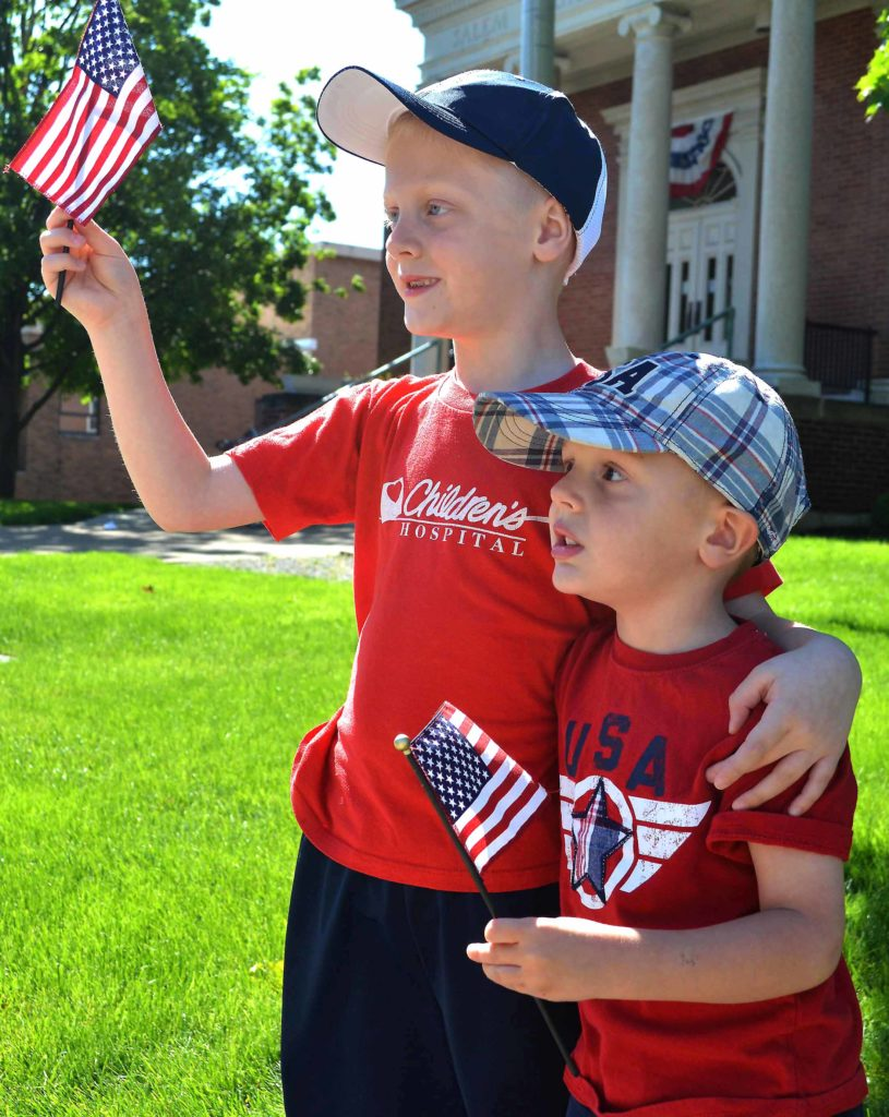 Six-year-old Eli and 4-year-old Logan Tice of Salem watch the parade while waving their flags. (Salem News photo by J.D. Creer)