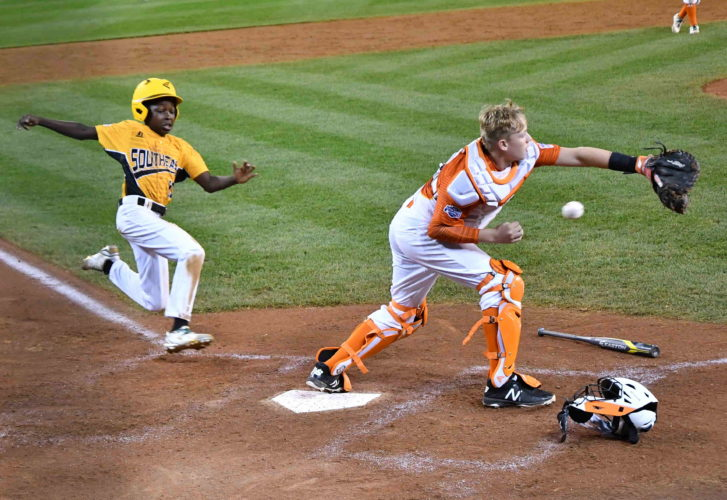 North Carolina's Cash Daniels-Moye scores as Texas catcher Chandler Spencer tries to field the throw for the winning run in extra innings at Lamade Stadium on Wednesday. (MARK NANCE/Sun-Gazette)