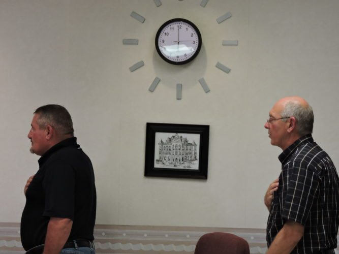 Photo by Shelley Hanson Bellaire Mayor Vince DeFabrizio recites the Pledge of Allegiance during council's Thursday meeting. On the wall in the background is a clock containing a camera that has caused controversy.
