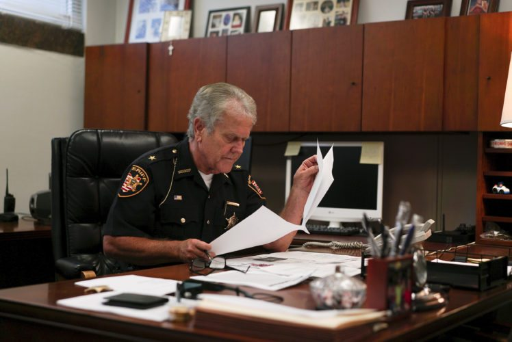 In this Aug. 9, 2017, photo, Lucas County Sheriff John Tharp looks through papers in his office in Toledo, Ohio. Police and rescue crews say drivers overdosing on heroin and other drugs are driving up the number of car crashes. Tharp says drivers in his county overdose on opioids so powerful it requires multiple doses of opiate antidote naloxone in order to revive them. (AP Photo/Dake Kang)