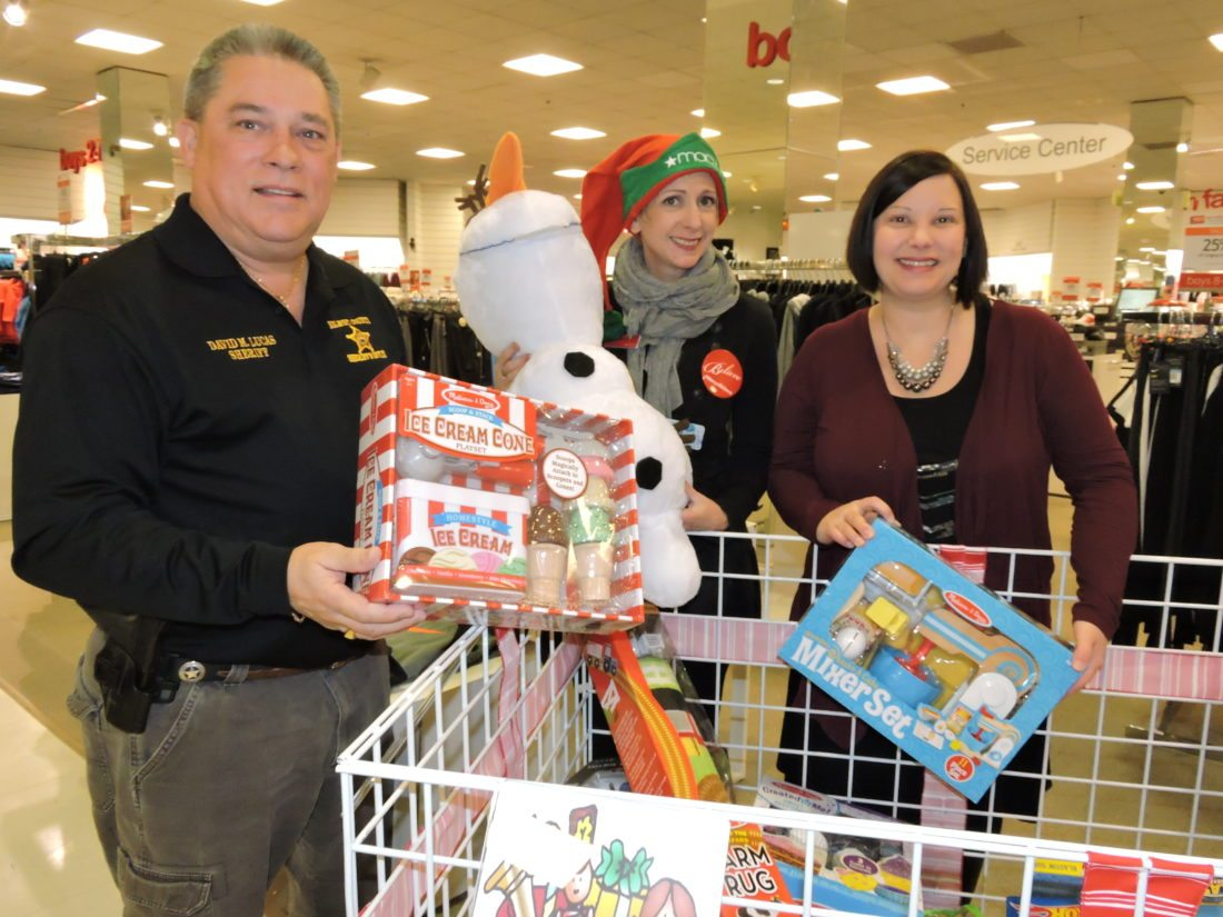 """Photo by Casey Junkins Busy preparing for """"Operation Toy Lift,"""" set for 8 a.m. to 4 p.m. Saturday at Macy's at the Ohio Valley Mall, from left, are Belmont County Sheriff Dave Lucas, Macy's store manager Jennifer Prietsch and mall Marketing Director Candi Noble-Greathouse."""