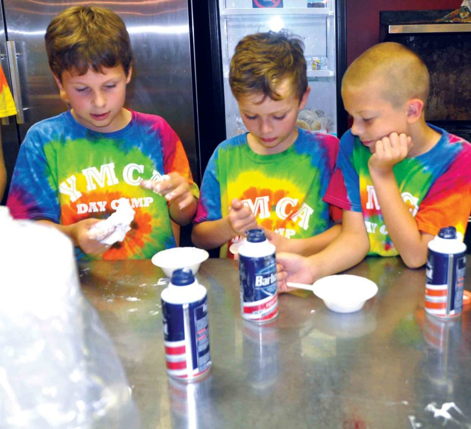 The Inter-Mountain photos by Angelea Goodwin YMCA Day Campers enjoy their afternoon by getting messy making 'slime' Wednesday. From left, Andrew Sproul, Derrick Bailey and Gage Koch are focused on making their slime the stickiest.