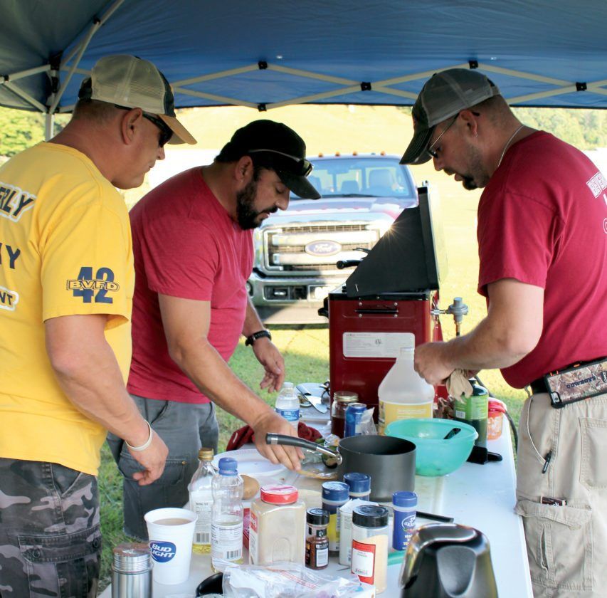 The Inter-Mountain photo by Brooke Binns Team Company 42, winners of the Beverly Fireman's Festival Cook off, work on the finishing touches of their entree during the annual Grill Off on Tuesday evening. The team prepared an orange chicken dish with macaroni and sweet pea salad and oatmeal brittle. Pictured are, from left, Kelly Cooper, Jimmy Harman and Jason Lanham.