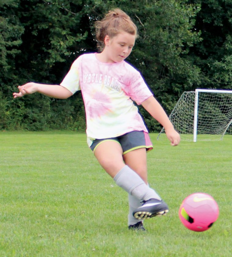 The Inter-Mountain photo by Brooke Binns Greylyn Belcher, a Seneca Soccer Under-10 player, works on using the inside of her foot during a passing drill on Tuesday evening.