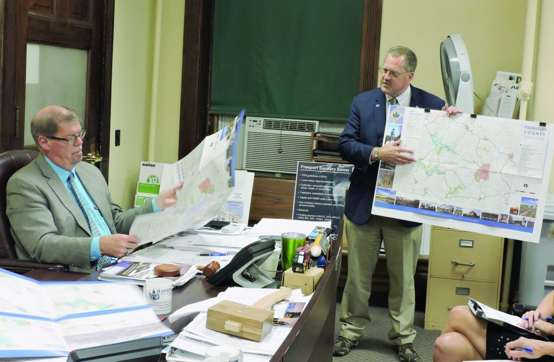 T-L Photos/CARRI GRAHAM DAN RICE, president of Ohio & Erie Canalway Coalition, right, reveals the finalized Harrison County Trail Plan for Harrison County to commissioners at last week's meeting. Commissioner Don Bethel reviews the plan. Upon completion, large numbers of hikers and bicyclists are anticipated to use the trail network.