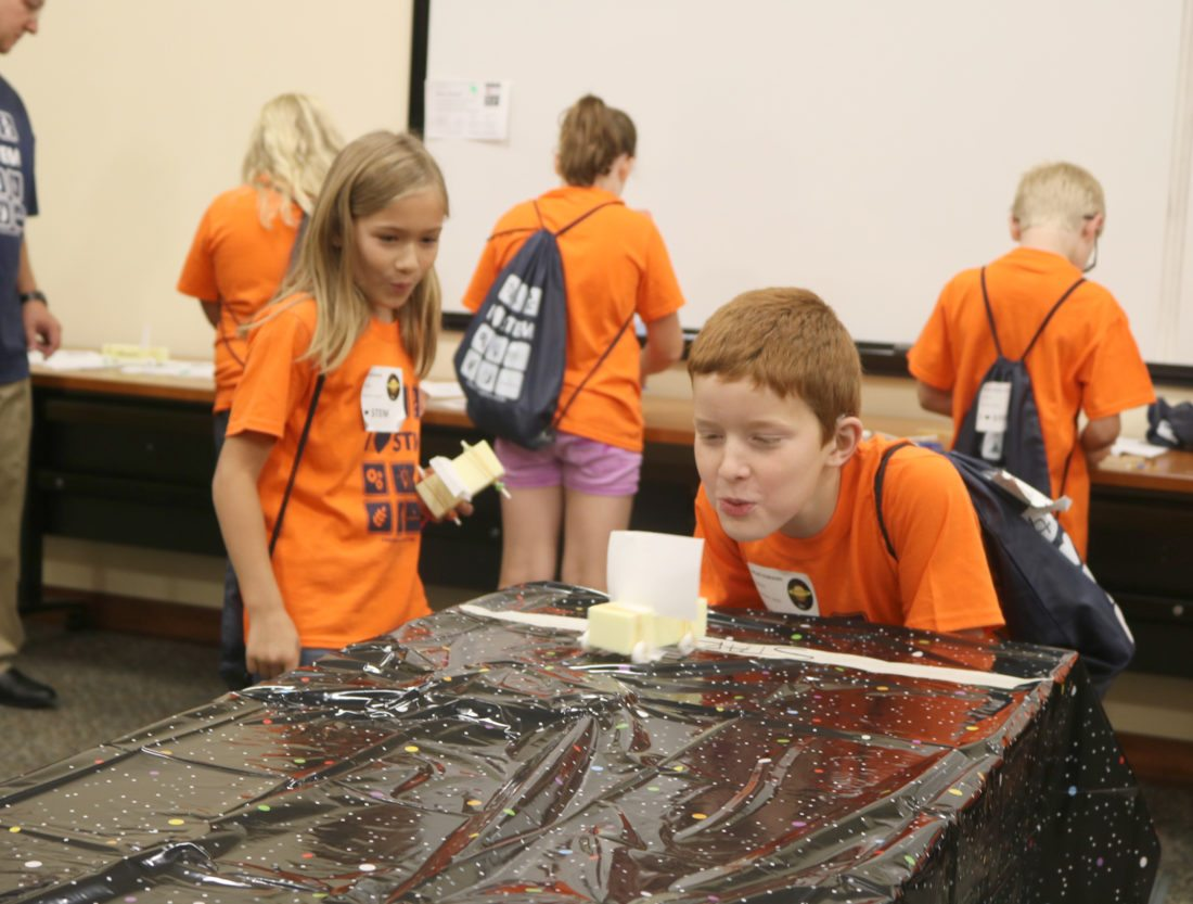 """T-R PHOTO BY ADAM SODDERS With sails attached to their """"Mars rovers,"""" STEM students at Emerson Friday took a deep breath and let loose a gust of wind to move their vehicles forward. To construct the rovers, they were given items like candy, paper and rubber bands."""