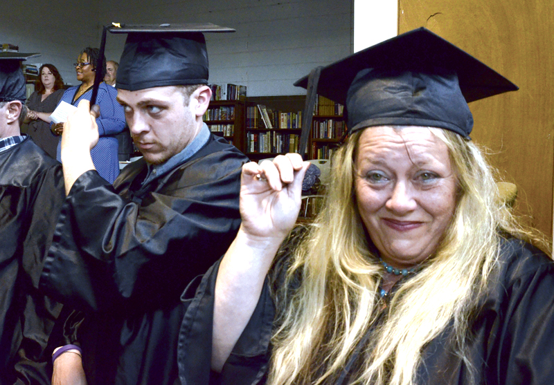 Tribune Chronicle / R. Michael Semple  GED graduates Gene Barr of Warren, left, and Misty Allen of Niles perform the tradition of moving their tassels across their mortorboards Friday as they graduate at Trumbull County Take Flight on Elm Road in Warren.