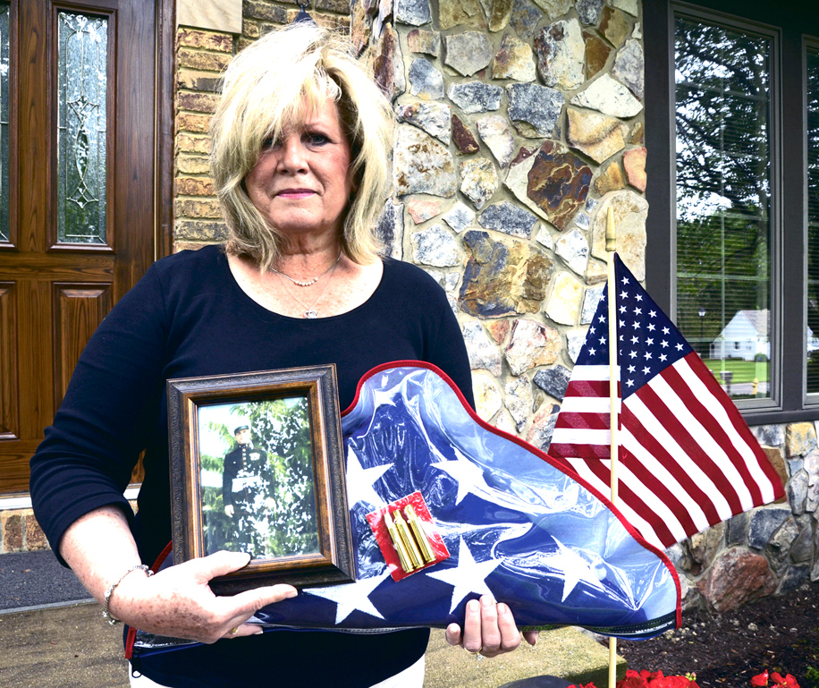 Tribune Chronicle / R. Michael Semple  Julie Fee of Champion holds a photo of her father, Marine Corps veteran Richard Kuszmaul, who died May 8. The flag and the bullets she is holding are from her father's military burial. Kuszmaul served in the Korean War.