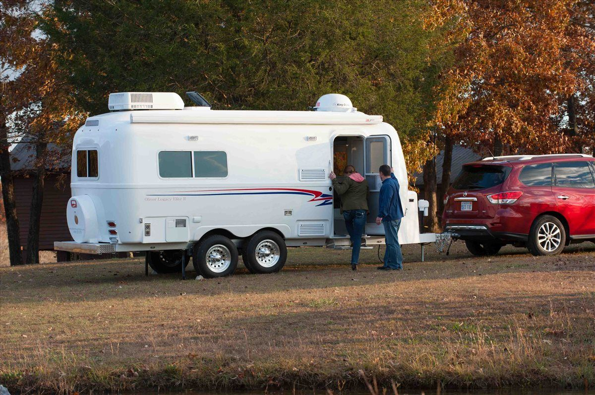 couple entering their oliver travel trailers legacy elite 2 during the fall