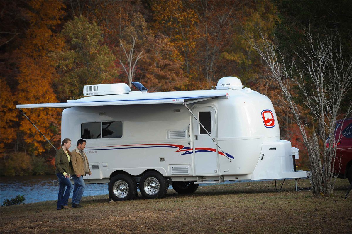 a couple enjoying their oliver travel trailers legacy elite 2 on lake during the fall