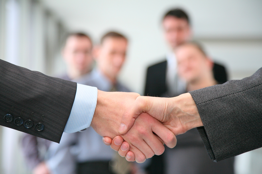 Shaking hands and business team in business a hall ** Note: Shallow depth of field