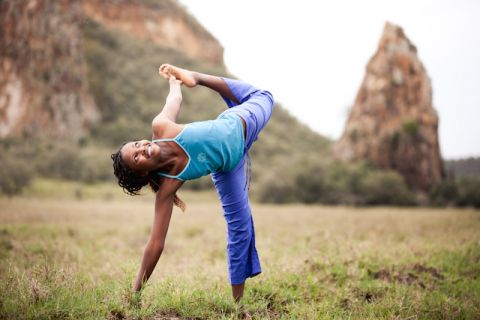 Nairobi local Eliam Wanji, in half moon pose, has been teaching yoga through AYP for the past five years. (Photo credit: Africa Yoga Project)