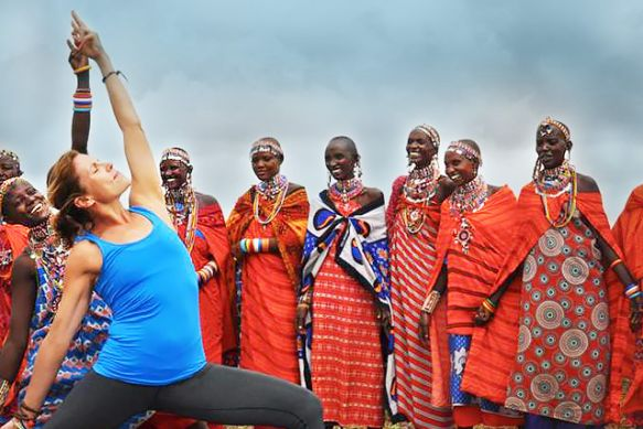A Seva Safari participant practicing yoga with members of the Maasai tribe in Amboseli National Park, Kenya. (Photo credit: Africa Yoga Project)