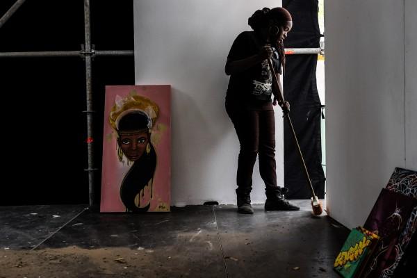 Dakar, Senegal (April 9) - Dieynaba Sidibe, Senegal's first female graffiti artist, sweeps an open gallery space at the Douta Seck Cultural House in Dakar, Senegal to help prepare for the official opening of Festigraff, a 10-day international graffiti festival held each year in the Senegal capital.