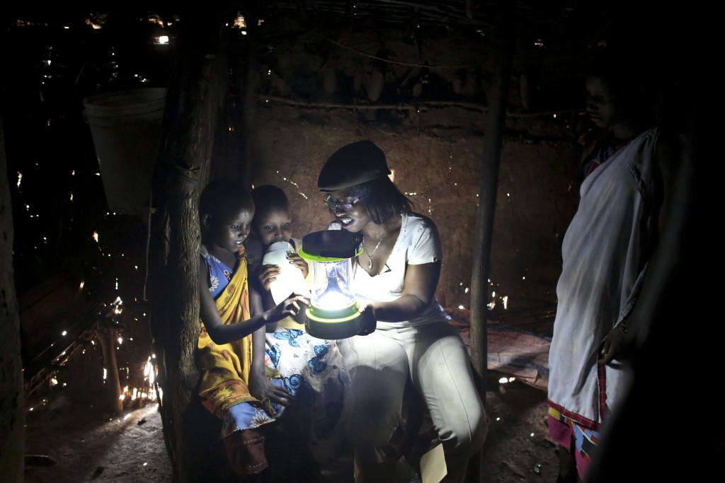 Jane Anika, right, from Green Energy Africa, a local NGO, shows two Maasai girls how to use a solar lamp, in the village of Koora, Kenya, on Tuesday, August 18, 2015. (Photo credit: Tara Todras-Whitehill)