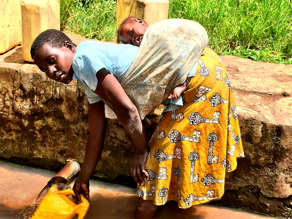 Mongo Alice and her baby fetching water. (Photo credit: Surge)