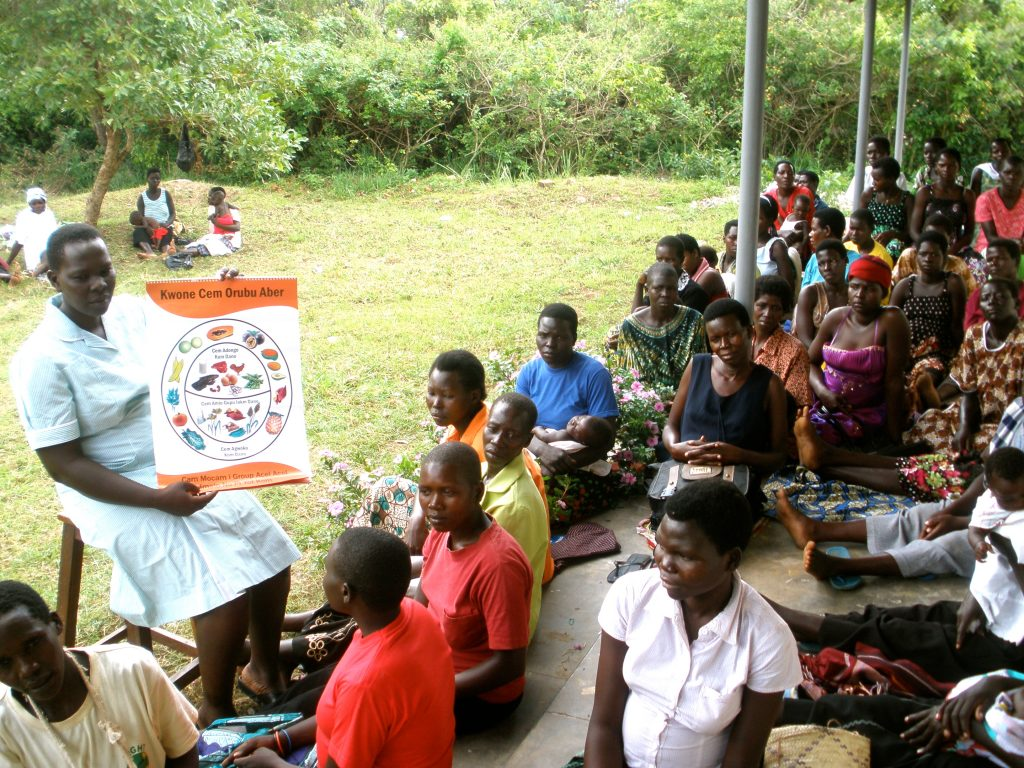 """""""Your child can achieve great things,"""" midwife Susan Ejang tells a gathering of new moms and moms-to-be at a clinic near Lira, Uganda. She is leading a nutrition class. Esther, pregnant at the time, is in the front row, wearing an orange shirt, three women to Susan's left."""