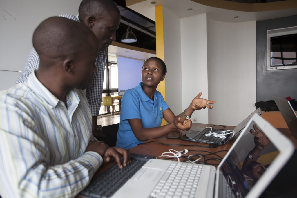 Lilian Uwintwali (right), co-founder of software development firm M-AHWII, consults with colleagues during development of their Agro-fiba app in Kigali, Rwanda. (Photo credit: Tom Gilks/ONE)