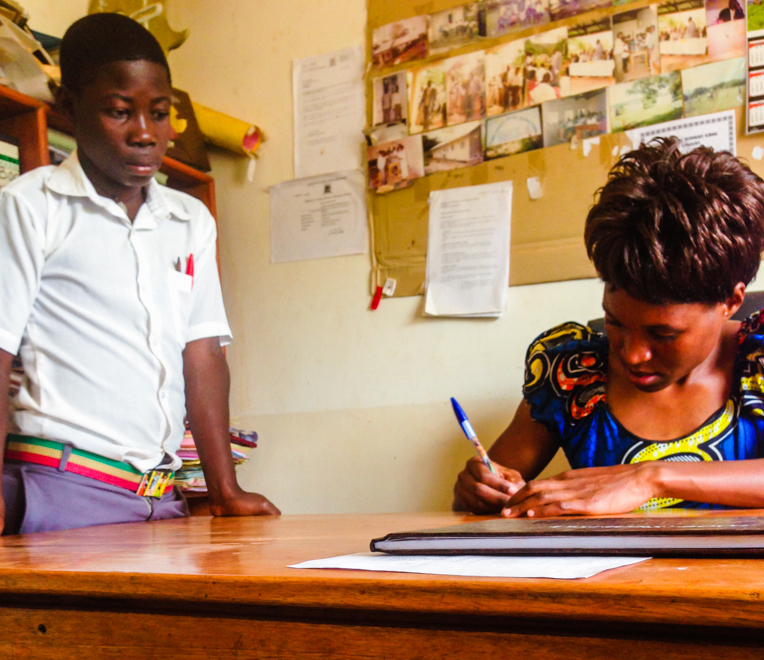 A Bujubuli teacher writes a student a note so he can have lunch, even though his tuition is not paid.