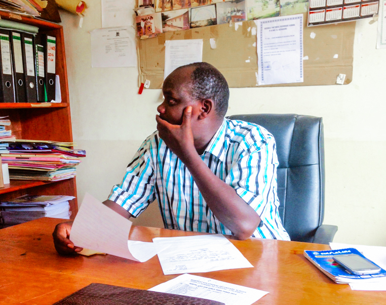 Headmaster Esau Ddungu sits in his office at Bujubuli.