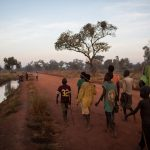At the first light of day, Sudanese refugees walk towards a lake formed by floodwaters near the town of Yida, South Sudan. They are looking for mudfish. Late in the rainy season, children from Yida arrive by the hundreds to fish at the temporary lake. © Andrew McConnell