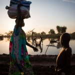 Shortly after dawn, two men cast a net in a shallow, seasonal lake near Yida, South Sudan. Mudfish are in abundance at this time of year, sometimes wriggling overland and eventually becoming trapped in small lakes like this one as floodwaters recede. © Andrew McConnell