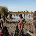 Hundreds of children displaced by fighting in Sudan and South Sudan look for mudfish in a seasonal lake near the town of Yida, South Sudan. The little money they earn from selling the fish helps support their families — and sometimes pays their school fees. © Andrew McConnell