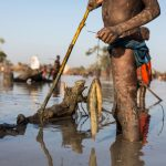 A young refugee from Sudan holds his catch of mudfish in a shallow lake formed by floodwater near the town of Yida, South Sudan. © Andrew McConnell