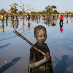 Yacob Ibrahim, a 10-year-old refugee from the Nuba Mountains in Sudan, fishes in a lake near Yida, South Sudan. Yacob's family fled Sudan three years ago and now live in Yida with thousands of other refugees. Like most of the children fishing here, he uses a stick to strike the fish when they surface.