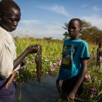 Kir Buth, 15, holds a fish caught moments earlier at a swamp near Yida, as Guor Path, 14, and Dictor Arak, 15, look on. Displaced by the fighting in South Sudan, the boys fish with their friends to raise money for schoolbooks and school fees.