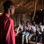 Second from right, Dictor Arak, 15, joins other students in a class at Yida Refugee Primary School in Yida, South Sudan. Dictor, who dreams of becoming a doctor, pays for his schoolbooks with the money he earns from catching and selling mudfish. © Andrew McConnell