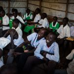 Guor Path, 14, and Miakol Kiir, 14, attend class with other pupils at Yida Refugee Primary School, in Yida, South Sudan. The boys catch fish to raise money for school fees and books.