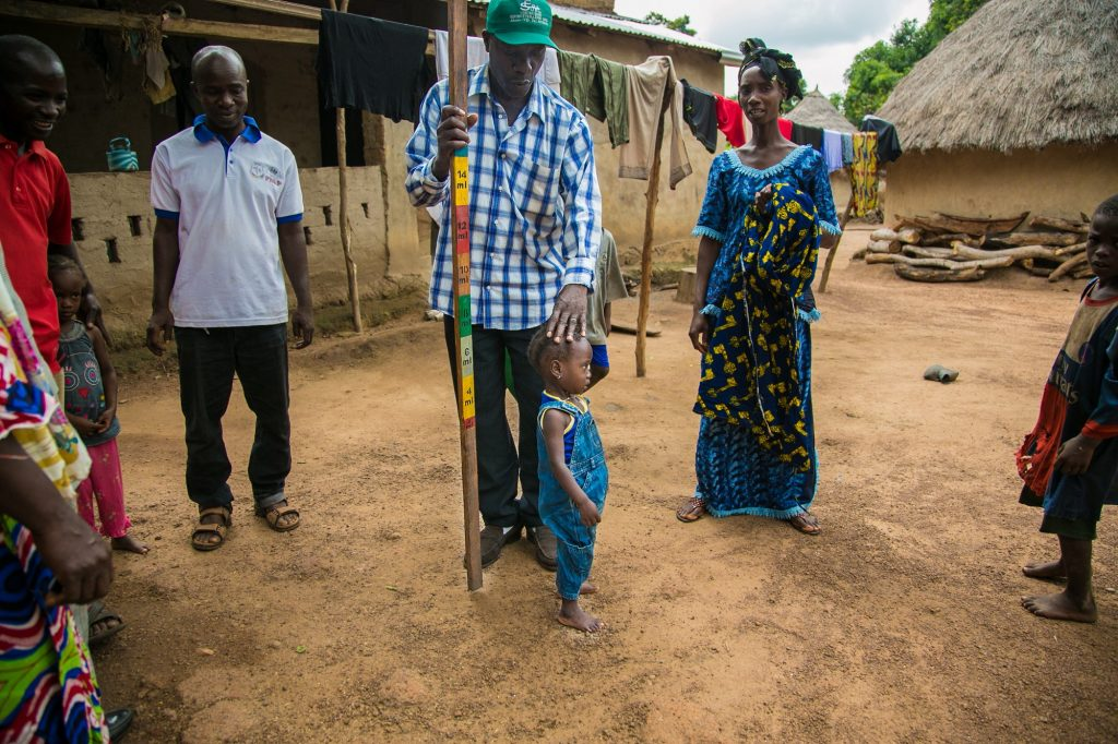 Toumany Conde, community health worker, demonstrates how he would measure a child in order to determine the correct medicine dose during a mass treatment campaign.