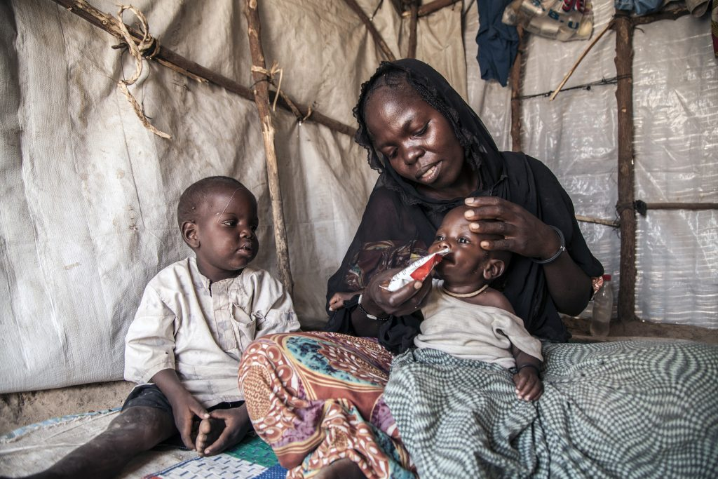 30-year-old Fanna Mohammed feeds her 7-month-old son, Umara Bukar, as her other son looks on at Muna Garage IDP camp, Maiduguri, Borno State, northeast Nigeria. (Photo credit: UNICEF)