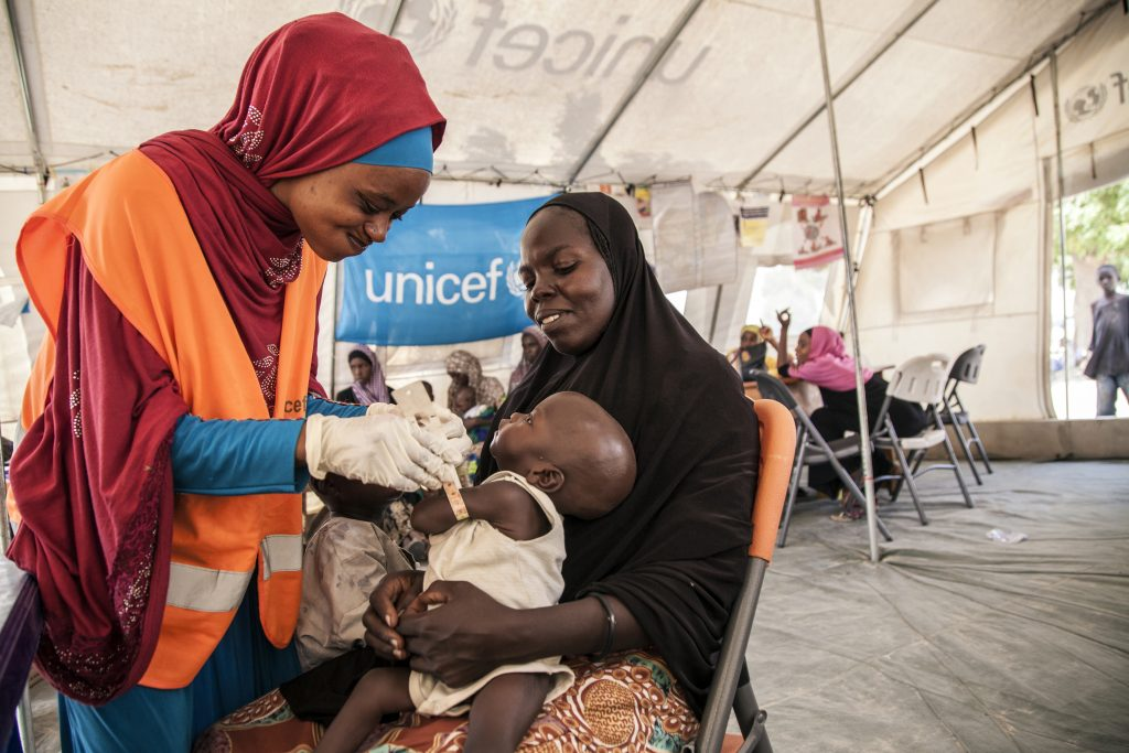 UNICEF Nutrition Officer Aishat Abdullahi assesses Umara for malnutrition at a UNICEF-supported health clinic at Muna Garage IDP camp, Maiduguri, Borno State, northeast Nigeria as Umara''s mother looks on. (Photo credit: UNICEF)