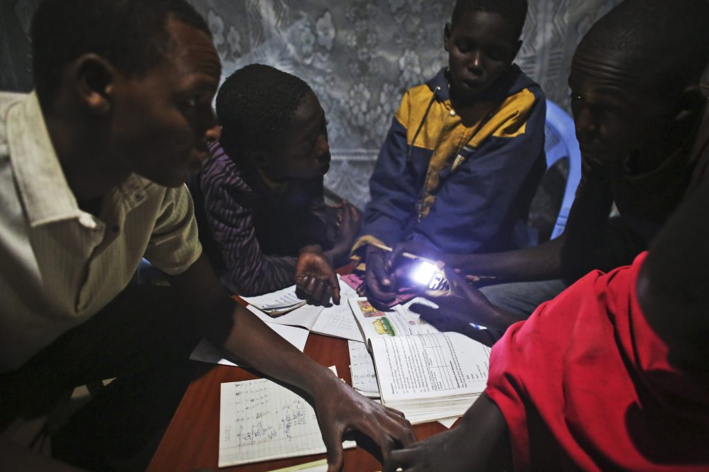 John Keko Mututua, age 16, left, studies with other children in his uncle's eco manyatta, a traditional home that has a solar panel which provides electricity after dark, in the town of Susua, Kenya. (Photo credit: Tara Todras-Whitehill)