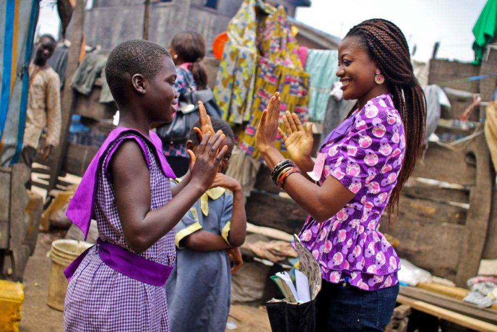 One of the Slum2School volunteer mentors plays with a student.