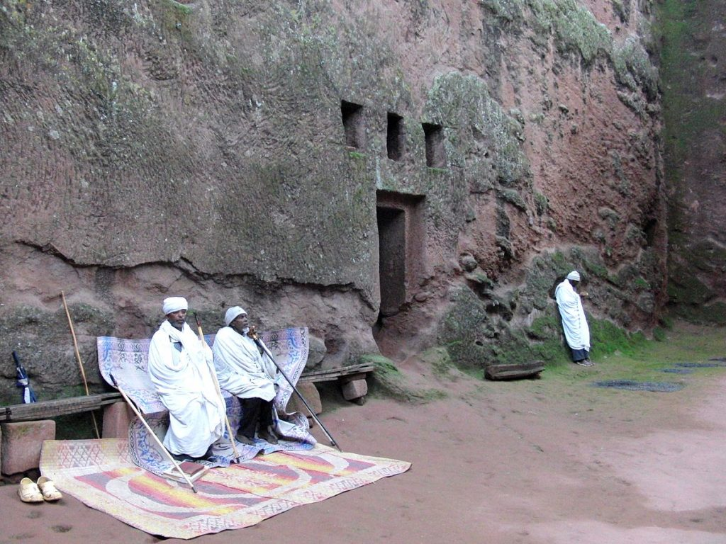 Monks sitting in front of the Bete Amanuel rock church in Lalibela, Ethiopia. (Photo credit: Jens Klinzing/Wikimedia Commons)